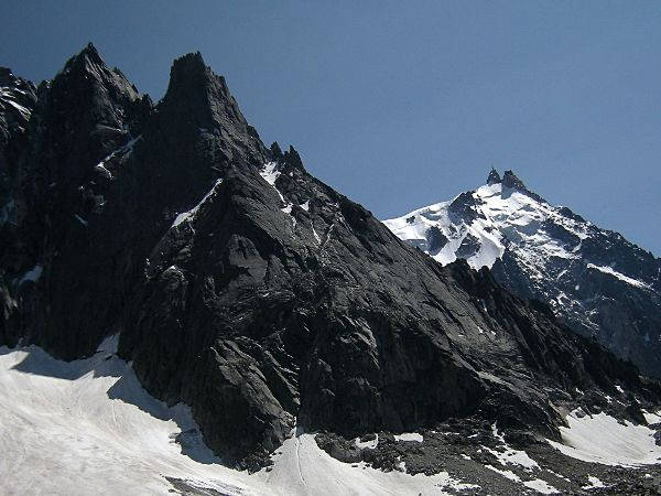 View of the north and west slopes of the Aiguille du Peigne, with on the left the Aiguille des Pélerins and in the background on the right the Aiguille du Midi. Photo source @wikipedia.com, licensed under CC BY-SA 3.0.
