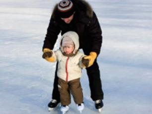 Father teaching his 2 year old child to skate in Les Houches
